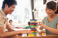Chinese couple playing with blocks in cafe