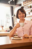 Chinese woman having coffee in cafe