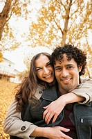 Couple hugging in autumn leaves
