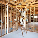 Hispanic construction worker measuring ceiling in unfinished room