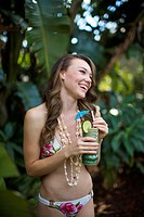 Woman with shell lei and cocktail in tiki glass