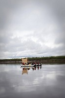 Group of boys in rafts using a tarp as a sail with a tilt shift lens.