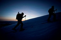 Silhouettes of two people backcountry skiing up a mountain at sunrise.