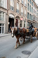 A Horse And Carriage Traveling Down A Narrow Street, Montreal Quebec Canada
