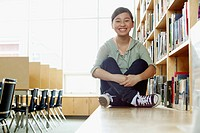Asian, middle school student sitting on bench in library