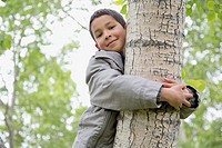 Male, elementary student hugging a tree.