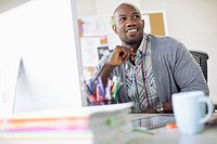 Handsome, African American creative professional at computer
