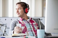 Male, creative professional listening to music.