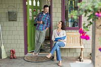 Middle-aged couple relaxing outdoors on porch (thumbnail)