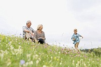 Grandparents watching grandson run in meadow