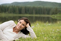 Portrait of pretty woman lying in meadow