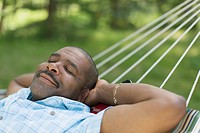 African American man relaxing in hammock.