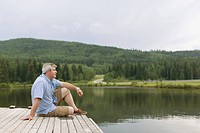 Middle_aged man sitting on boat dock with pc tablet
