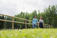 Middle_aged couple walking along corral fence