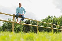 Handsome, middle_aged man sitting on corral fence