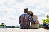 View from behind of middle_aged couple cuddling on deck