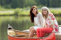 Portrait of women sitting at the end of boat dock