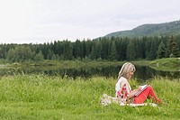Middle_aged woman sketching in meadow by water