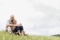 Attractive, mature couple sitting in meadow together