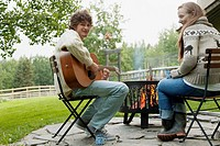 Young man playing guitar for girlfriend by a fire