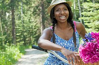 Pretty, African_American woman biking along rural path