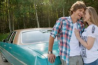 Young couple cuddling by vintage car