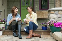 Mother and daughter enjoying coffee outside front of house