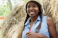 Pretty, African_American woman in straw hat by hay bale