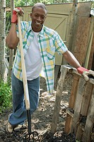 Mid_adult, African_American man holding pitchfork on rural property