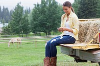 Young woman texting while sitting on truck tailgate