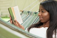 Pretty, African_American woman reading book in hammock