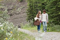Young adult couple walking with picnic basket and fishing gear