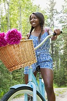 Pretty, young adult woman bicycling on rural property
