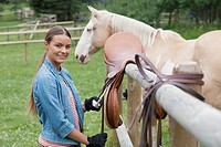 Young woman with saddle by horse paddock