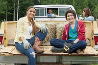 Teen and pre_teen children sitting on tailgate of dad's truck