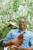 Mid_adult African_American man holding chicken and smiling