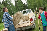 Dad and son loading hay bales onto truck
