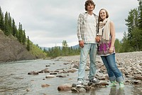 Young adult couple holding hands by stream