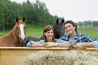 Middle_aged couple standing by truck with two horses
