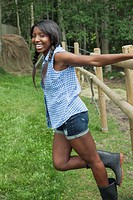 Young, African_American woman holding fence and smiling at camera