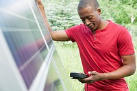 Mid_adult man checking solar panel with volt meter