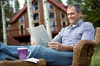 Handsome man reading newspaper outdoors