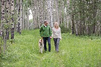 Middle-aged couple walking dog in woodland (thumbnail)