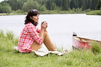 Pretty, middle_aged woman sipping coffee by waterfront