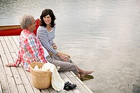 Mature couple enjoying wine together on their dock