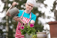 Middle_aged woman watering flowers outdoors