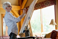 Middle-aged woman painting on canvas in her cottage (thumbnail)