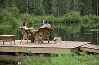 Middle-aged couple toasting with wine on their dock (thumbnail)