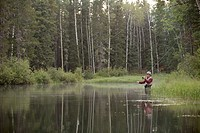 Middle-aged man fly fishing on rural property (thumbnail)