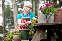 Mature woman using pc tablet for gardening information (thumbnail)